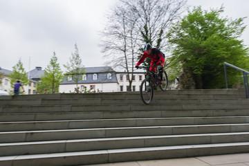 Fahrradfahrer fährt Streppenstufen hinab