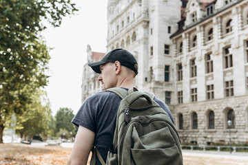 A young man or tourist or student with a backpack looks at the sights in Leipzig in Germany.