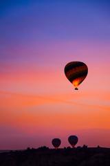 Beautiful hot air balloons flying over Cappadocia landscape at sunrise