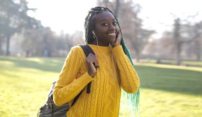 Pretty girl walking in a park, listening music with earphones