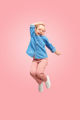 Young happy caucasian teen girl jumping in the air, isolated on pink studio background. Beautiful female full length portrait. Human emotions, facial expression concept.