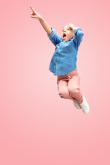 Young happy surprised caucasian teen girl jumping in the air, isolated on pink studio background. Beautiful female full length portrait. Human emotions, facial expression concept.