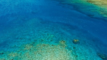 stunning aerial drone image of a great coral reef marine channel in calm weather flat water and incredible colorful sea ocean bed around a small remote isolated tropical island