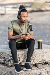 Black man listening to music from smartphone