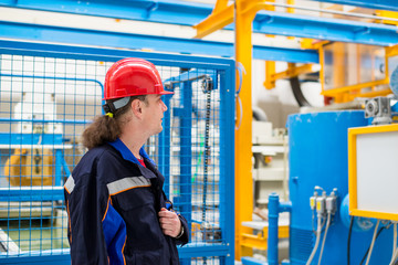 Worker in a factory looking at factory machine