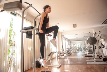sport, fitness, lifestyle and people concept - woman exercising and doing pull-ups on bar in fitness center - Image