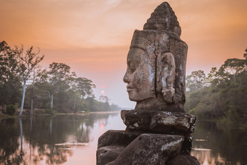 Stores à enrouleur Con. ancienne Stone Asura on causeway near South Gate of Angkor Thom in Siem Reap, Cambodia. Beautiful sunset over ancient moat in background. Angkor Thom is a popular tourist attraction.