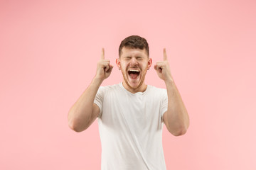 Wow. Attractive male half-length front portrait on pink studio backgroud. Young emotional surprised bearded man standing with open mouth. Human emotions, facial expression and advertising concept