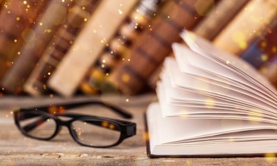 Open book and glasses on wooden table