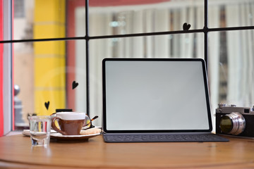Creative photographer desk with mockup blank screen tablet and vintage camera