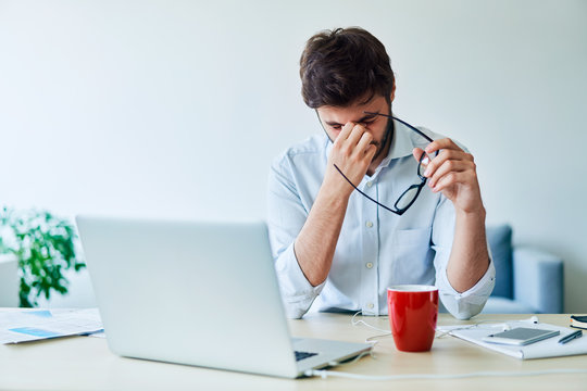 Young businessman having headache while working in home office
