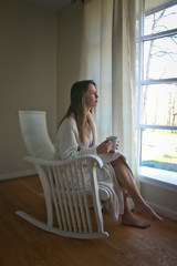 A young woman sits in a rocker drinking coffee and gazes out a window.