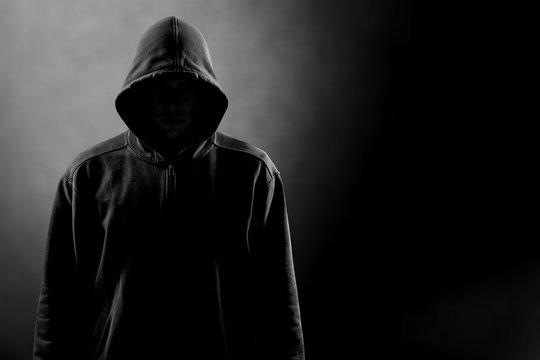 Dark unrecognisable man in hoodie on background