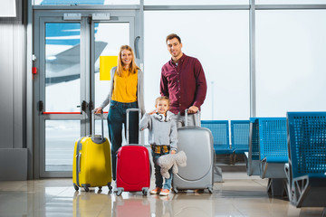 cheerful family standing with luggage in waiting hall of airport