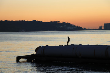 Man walking in a jetty with a river in background at the sunset. Lisbon Portugal