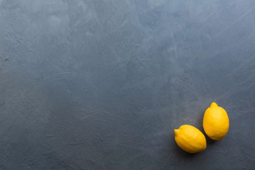 Fresh ripe lemons on dark stone background. Top view with copy space.