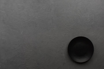 Black plate on dark stone background. Copy space, top view.