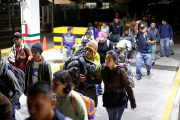 People belonging to a caravan of migrants from Honduras en route to the United States, walk at the border crossing to Mexico in Hidalgo