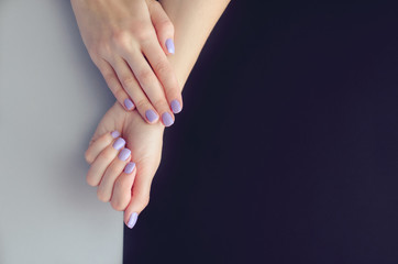 Female hands with a manicure on a black-gray background.