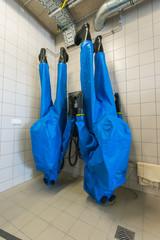 Schutzanzüge mit Stiefeln hängen zum Trocknen