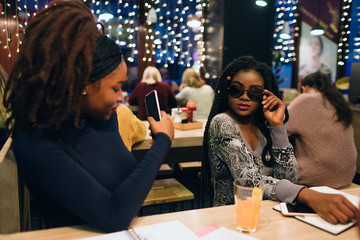 Picture of african model posing for pictures. She hold hand on sunglasses. Her friend take photos on phone. they sit inside.