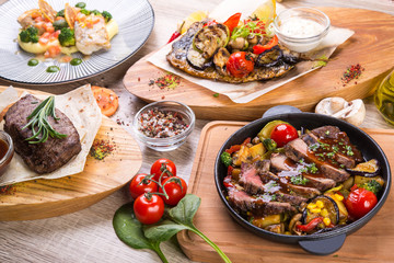 Table lined with dishes steak, roast beef in pan, mackerel with grilled vegetables