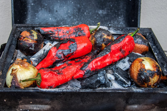 Fresh grilled vegetables on charcoal. peppers and onion roasting over a charcoal grill