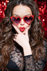 The girl in sunglasses in the shape of a heart from the lips folded the heart