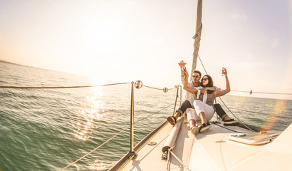 Young lovers couple on sail boat with champagne at sunset - Exclusive luxury concept with rich millennial people lifestyle on tour around the world - Soft backlight focus on warm sunshine filter