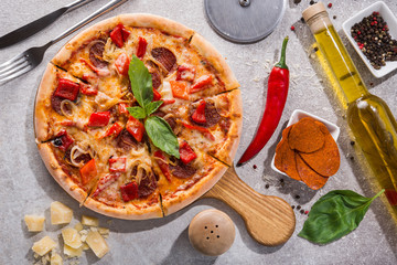Hot pizza with ham salami, pepper and chili