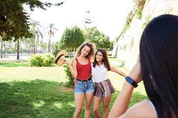 Spain, Mallorca, Palma, woman taking picture of best friends while having fun in a park in summer