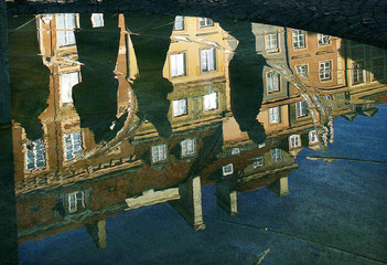A reflection of people taking a walk through the old town of Warsaw.