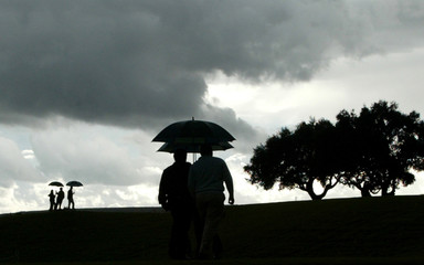Spectators walk to shelter after play was suspended due to rain during Volvo Masters Golf at Valderrama.