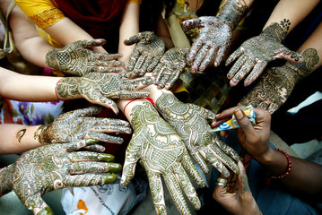 Indian women display their hands decorated with henna on the eve of Karva Choth festival in Chandigarh.