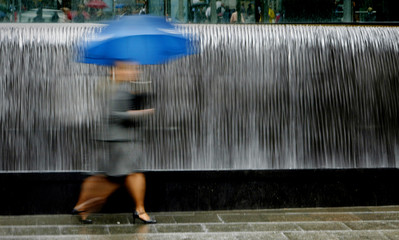 A pedestrian hurries through the rain in front of a fountain in central Sydney.