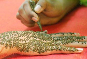 A Malaysian Hindu paints her hand with henna ahead of Diwali celebration in Kuala Lumpur.