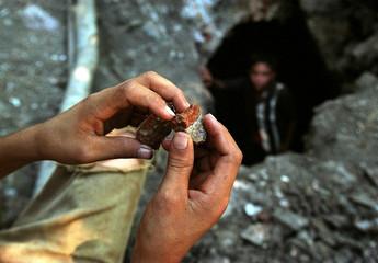 A Nicaraguan child inspecting a half split rock outside the La Indian mine in Nicaragua.