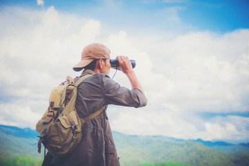 Young professional traveler man with binoculars, fantastic mountain landscape