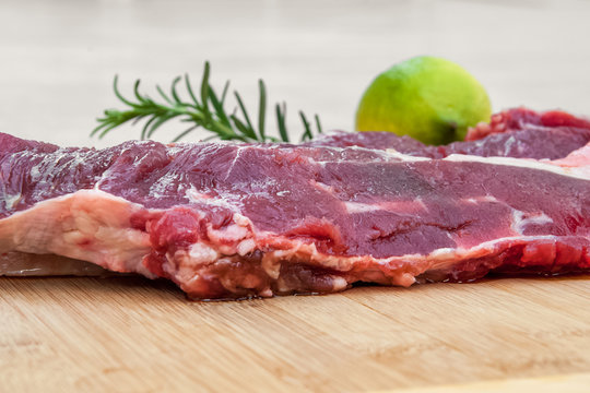 fresh beef meat on a cutting board with lemon and rosemary