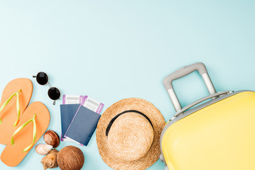 top view of straw hat, coconut, flip flops, seashells, sunglasses, passports, air tickets and travel bag on blue background