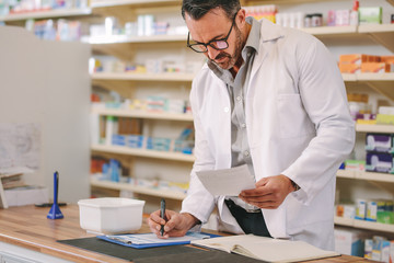 Foto op Canvas Apotheek Pharmacist writing prescription pharmacy counter