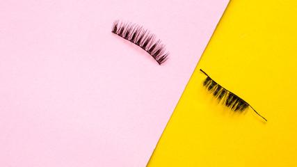 Eyelashes on pink and yellow background