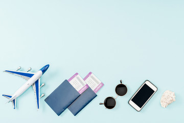 top view of passports, air tickets, toy plane smartphone with blank screen, seashells and sunglasses on blue background