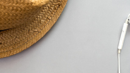 Hat wicker and earphone on gray background