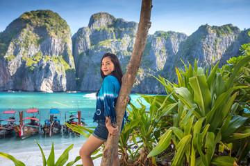 Young asian woman posting on the Maya bay