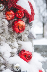 Red decorations on a Christmas tree on a snowing day