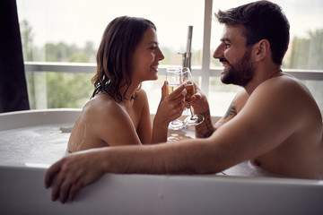 Romantic couple enjoying and relaxing in the bathtub and drinking champagne .