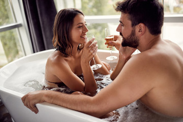 Attractive boy and girl enjoying and relaxing in the bathtub and drinking champagne .