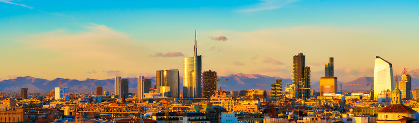 Milan skyline at sunset. Large panoramic view of Milano city, Italy. The mountain range of the Lombardy Alps in the background. Italian landscape.