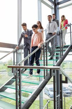 business people walking down stairs.